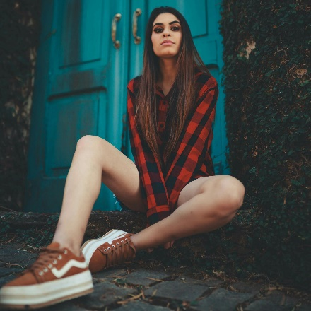 Photo of Woman in Red Plaid Shirt Sitting on the Ground In Front of Blue Door